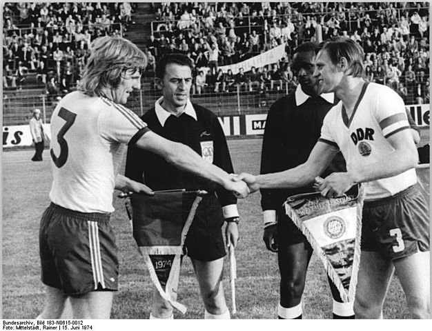Peter Wilson and Bernd Bransch swap pennants before Australia's first game at the World Cup Finals