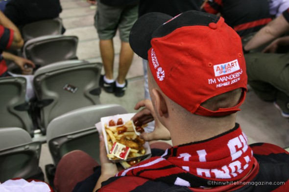 A WSW fan doing what he's told - sitting down, eating in-stadium food, wearing official merchandise.