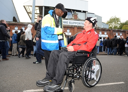 A wheelchair-bound Fulham fan talks with a steward.